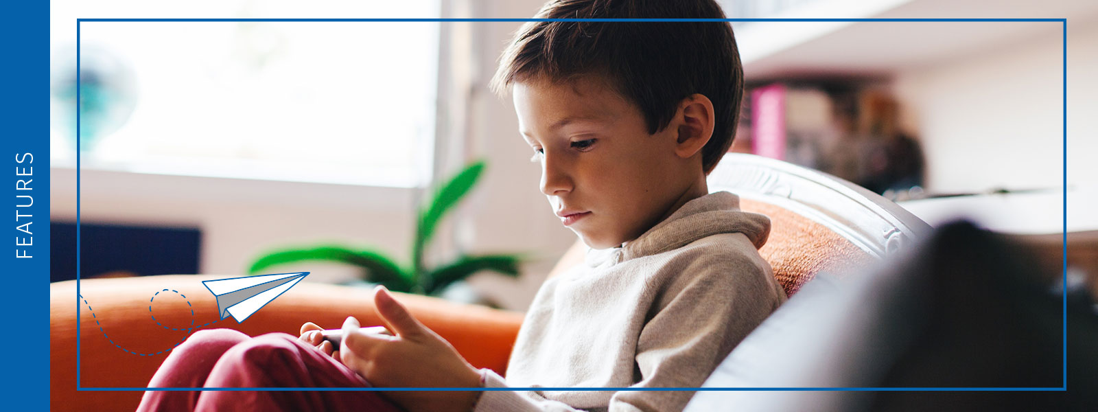 A young boy sits on a couch totally engaged in the Accessit library system that he is accessing from his tablet device