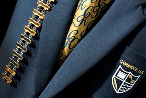 A Cambridge High School blazer and tie worn by a high achieving student with his many honours pinned to his jacket