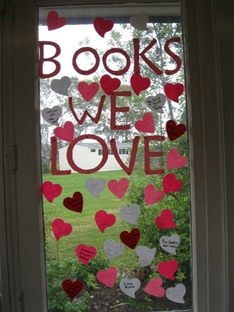 """This image shows red and white paper love hearts and the words """"Books we love"""" in red on a glass door, looking out on to a lawn with bushes."""